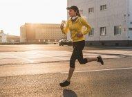Mujer joven que corre en una calle al atardecer - foto de stock