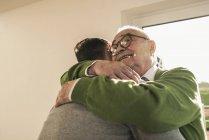 Усміхнений старший чоловік обіймає молодого чоловіка — стокове фото