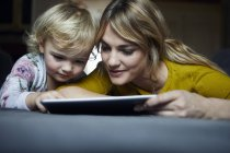 Портрет матери и дочери с помощью планшета дома — стоковое фото