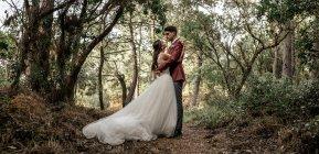 Наречений і наречена стоячи в лісі охоплює — стокове фото