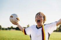 Menino vestindo camisa de futebol alemão gritando de alegria, de pé em salpicos de água — Fotografia de Stock