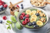 Buddha bowl of green chia pudding with slices of banana, blueberries, raspberries and walnuts — Stock Photo