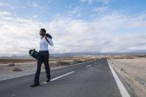 España, Tenerife, joven empresario con monopatín caminando por carretera - foto de stock