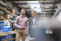 Hommes d'affaires lors d'une réunion dans le hall de production — Photo de stock