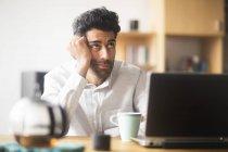 Retrato del empresario pensante en el escritorio de su oficina - foto de stock