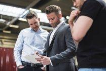 Three men sharing tablet on factory shop floor — Stock Photo