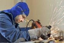 Arbeiter benutzt Winkelschleifer in Fabrik — Stockfoto