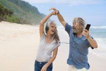 Couple sénior beau avec écouteurs dansant sur la plage — Photo de stock