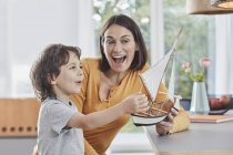 Feliz madre e hijo jugando con el barco modelo en casa - foto de stock