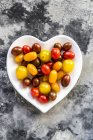 Heart-shaped bowl of mini tomatoes — Stock Photo