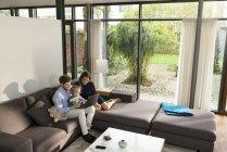 Los padres y el hijo se sientan en el sofá en la sala de estar moderna utilizando el ordenador portátil en casa - foto de stock