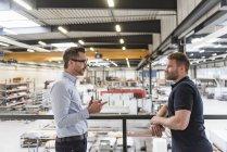 Двое мужчин разговаривают на заводе — стоковое фото
