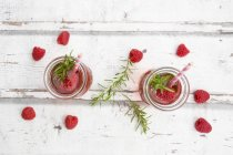 Two glass bottles of homemade raspberry lemonade flavoured with rosemary — Foto stock