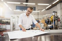 Mature businessman in factory working on plan — Stock Photo