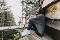 Молодая женщина сидит в деревянном доме на природе расслабляющий — стоковое фото