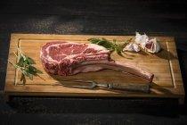 Raw tomahawk steak, garlic and herbs — Stock Photo