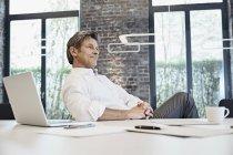 Uomo d'affari maturo con laptop in ufficio moderno — Foto stock