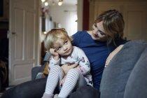 Мать и маленькая дочь сидят вместе на диване дома — стоковое фото