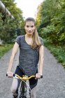 Портрет спортивной молодой женщины с велосипедом в парке — стоковое фото