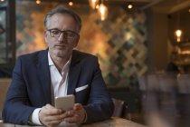 Ritratto di uomo d'affari che utilizza lo smartphone in un ristorante — Foto stock