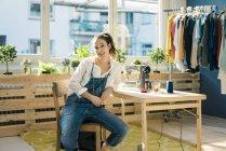 Portrait of smiling fashion designer sitting at desk in her studio — Stock Photo