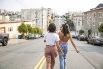 Due giovani donne che camminano per strada — Foto stock