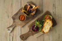 Dos platos de madera con patatas fritas y boniato caseras, salsa de tomate y pan crujiente con ensalada, jamón y remolacha - foto de stock