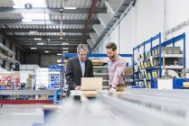 Businessmen using laptop in production hall — Stock Photo