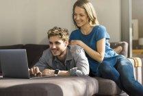 Улыбающаяся пара с помощью ноутбука на диване дома — стоковое фото