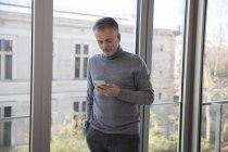 Бизнесмен, использующий смартфон дома — стоковое фото
