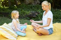Girl with mother practicing yoga on blanket — Stock Photo