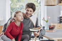 Felice padre e figlia giocare con il modello di barca a casa — Foto stock