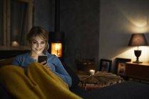 Портрет улыбающейся женщины со смартфоном, отдыхающей на диване вечером — стоковое фото