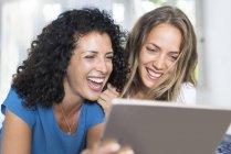 Deux femmes heureuses regardant la tablette — Photo de stock