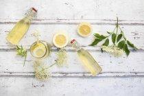 Sirup di fiori di sambuco fatti in casa, fette di limone, foglie e fiori di sambuco — Foto stock