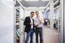 Dois empresários com tablet na fábrica — Fotografia de Stock