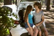 Молода пара сидить у машині в лісі. — стокове фото