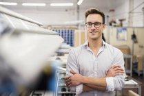Portrait de jeune homme d'affaires souriant dans l'usine — Photo de stock