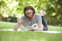 Homem lendo livro sobre cobertor em um parque enquanto come salada de macarrão — Fotografia de Stock