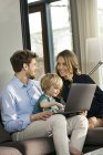 Smiling parents and son sitting on sofa with laptop at home — Stock Photo