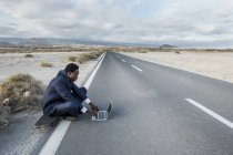 España, Tenerife, joven empresario sentado en monopatín y usando portátil - foto de stock