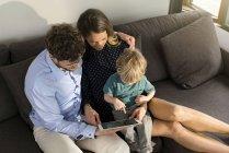 Pais e filho sentados no sofá segurando tablet em casa — Fotografia de Stock