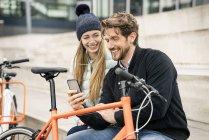 Усміхнена пара з велосипедами та стільниними телефонами в місті — стокове фото