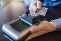 Hombre usando lector de tarjetas de crédito, primer plano - foto de stock