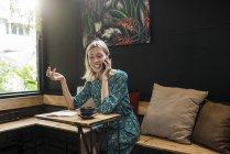 Junge lächelnde Frau mit grünem Kleid sitzt im Café und spricht mit jemandem auf ihrem Smartphone — Stockfoto