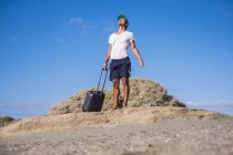 Man standing with rolling suitcase at the beach — Stock Photo