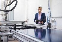 Зрелый бизнесмен на солнечной фабрике держит папку — стоковое фото