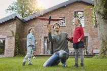 Отец с двумя детьми, играющими в игрушечный самолет в саду своего дома — стоковое фото
