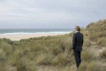 Reino Unido, Cornwall, Hayle, empresário de pé em dunas de praia e olhando para a vista — Fotografia de Stock