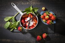 Sugared fresh strawberries in pot, bourbon vanilla beans and mint — Stock Photo
